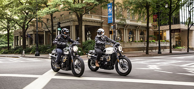 Two people riding on two Street Scramblers through a city street.