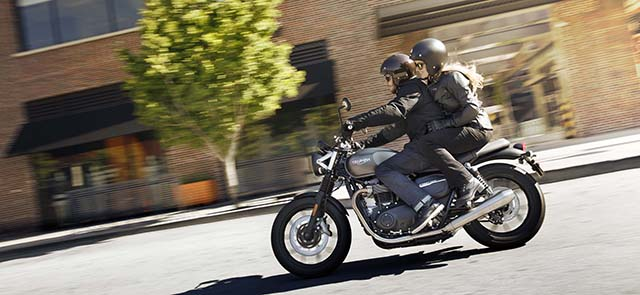 Two people riding on a Street Twin through downtown.