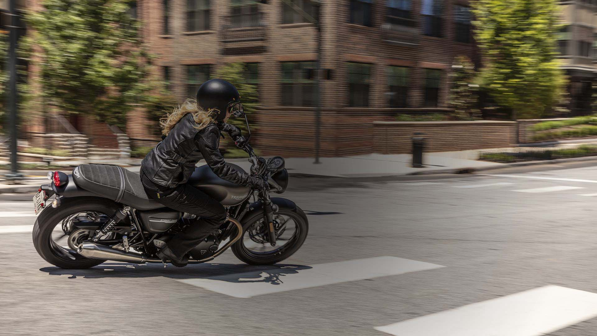 Person riding a Street Twin through the city streets.