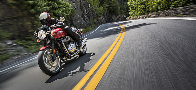 Person riding a Thruxton through the winding mountain roads.
